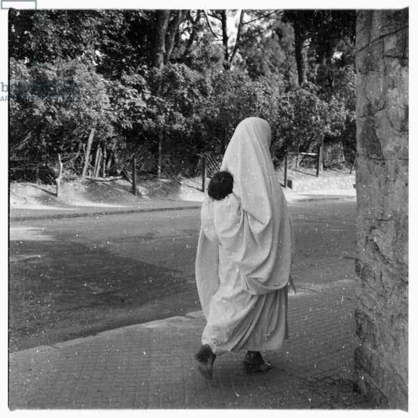Woman with child on back walking down street, Tangier, early 1960's (b/w photo)