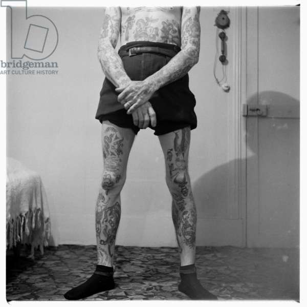 Cash Cooper, tattoo pioneer, portrait of the Soho tattoo artist pioneer Cash Cooper showing his tattoos, Soho, London, early 1960's