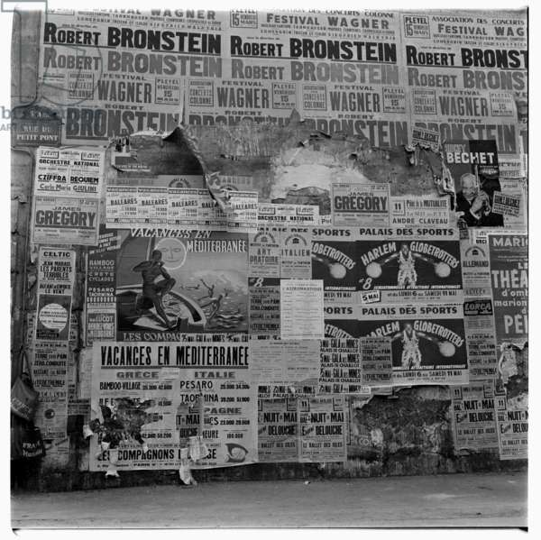 Image of wall covered in posters including the Harlem Globetrotters, Rue de Petit Pont, Left bacnk, latin Qwuarter, Paris early early 1950's