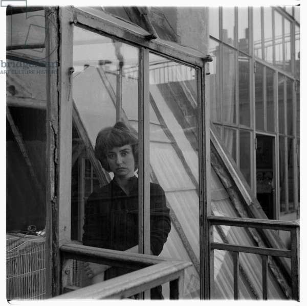Pegeen Vail Guggenheim, portrait of Pegeen Guggenheim, daughter of Peggy Guggenheim, wife of situationist painter Ralph Rumney, step-daughter of Max Ernst, in her home in Paris, France mid 1950's (b/w photo)