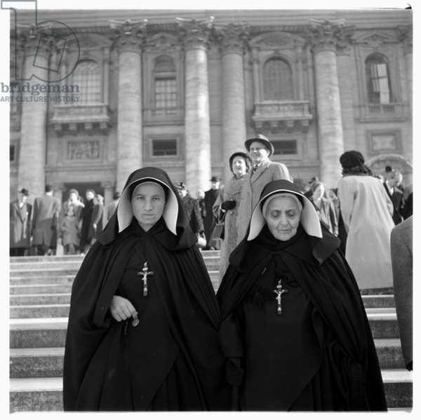 Portrait of two hard faced nuns descending stairs, in full holy habit and crucifix, St.Peters Square, Rome early early 1950's