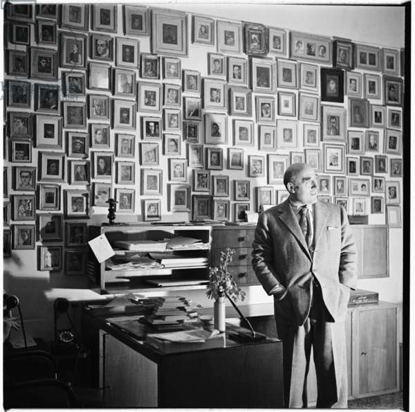 Cesare Zavatinni, portrait of neorealist screenwriter, writer and painter in front of his collection of postcard oil portraits, Rome, mid 1950's (b/w photo)