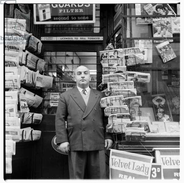 Tony Abbro, newsagent, portrait of Tony Abbro outside his newsagent shop, Old Compton Street, Soho London, December 1960 (b/w photo)