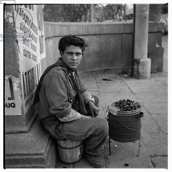 Image of a street urchin vendor selling roasted chestnuts, venditore ambulante di castagne, Rome, early 1950's