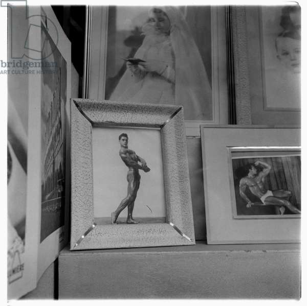 Image of a photographers window showing beefcake muscle posing images alongside first communion, Rome, early 1950's