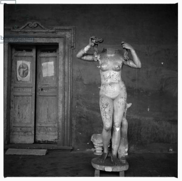 Image of a classical Roman nude female statue holding her long hair, with a comically missing head, possibly Rome or Paris, early early 1950's