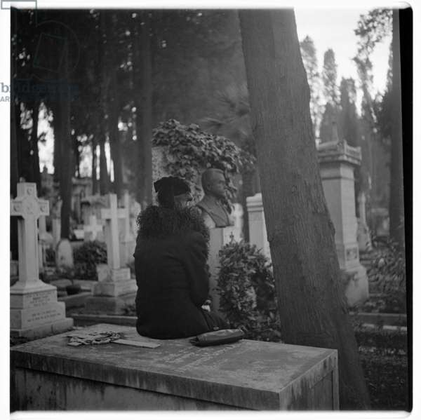 Image of lone woman sat on a grave, Cimetiere de Montarnasse, Paris early early 1950's