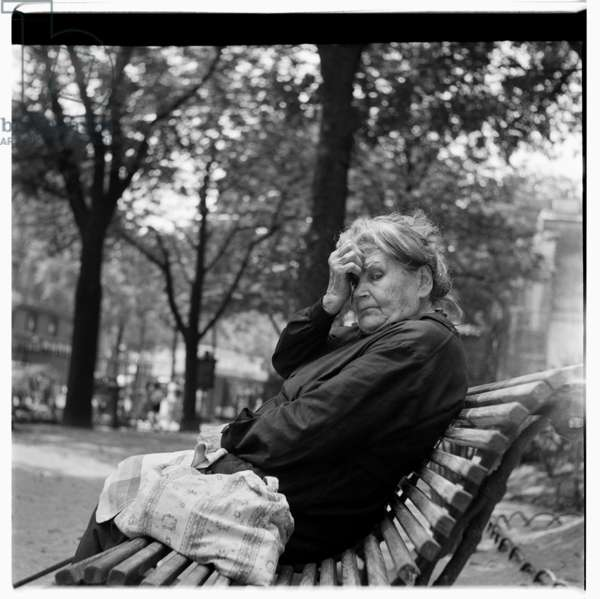 Portrait of a thoughful old woman resting in park on bench, early early 1950's, Paris