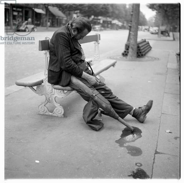 Image of a sleeping clochard or down and out with wooden leg on park bench, Paris early 1950's