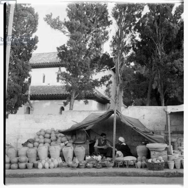 Man selling pots by the roadside, Tangier, early 1960's (b/w photo)