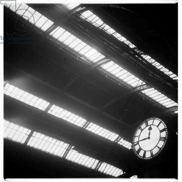 London, Train station clock, image from a night walk round central London, showing Kings Cross station clock, London 1957