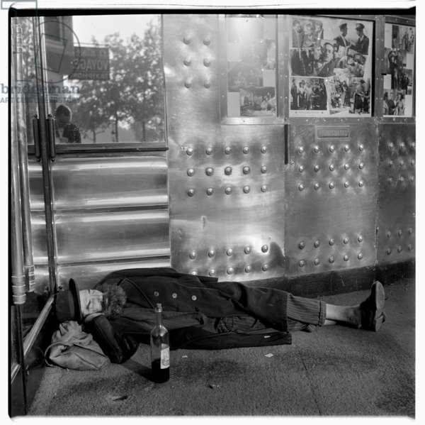 Image of a sleeping drink, wine bottle alonmgside, in bus shelter, Paris early 1950's