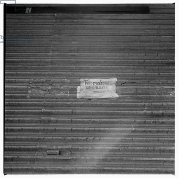 "Image of shop rollershutter door, with handwriten sign ""Le magasin est ouverte cette apres midi - the shop is open this afternoon"", Paris early early 1950's"