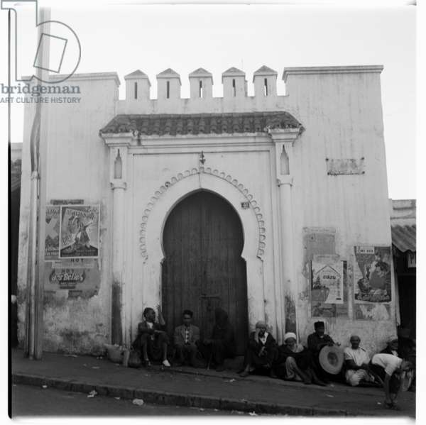 People sitting in front of a building, Tangier, early 1960's (b/w photo)