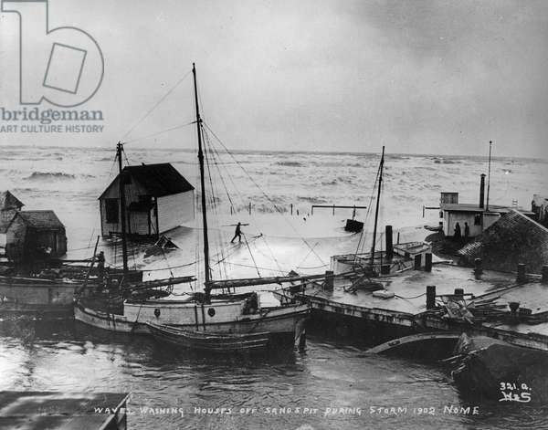Waves washing houses off Sandspit, Nome, during storm, from 'One Man's Gold Rush: A Klondike Album' by Murray Cromwell Morgan, 1902 (b/w photo)