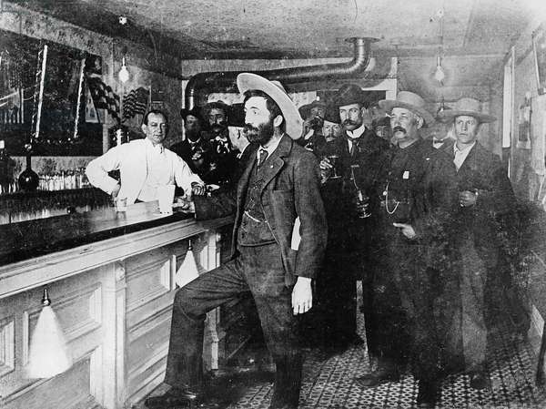 Group of men drinking in a saloon, from 'One Man's Gold Rush: A Klondike Album' by Murray Cromwell Morgan (b/w photo)