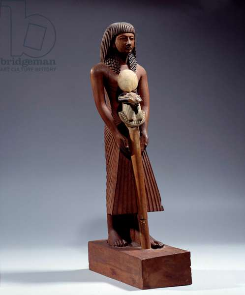 Egyptian antiquite: statue of a man bearing a divine sign at the head of a belier. Wooden statuette from the Ramessid period, New Empire (circa 1550-1069 BC). Sun 0,42 m Paris, Musee du Louvre