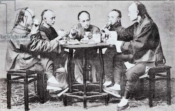 Chinese family at table Photograph of the beginning of the 20th century.