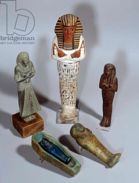 """Egyptian Antiquities: stone or wood funerary statuettes of different sovereigns (Ramses III standing on the right, of Ptahmes, standing on the left, Ramses IV standing on the centre) Ouchebti signifying """""""" repondant"""""""") designed the funeral servants who were to answer Osiris's call and replace the dead in the field work of the beyond. 1300 -1500 BC. Paris, Louvre Museum"""