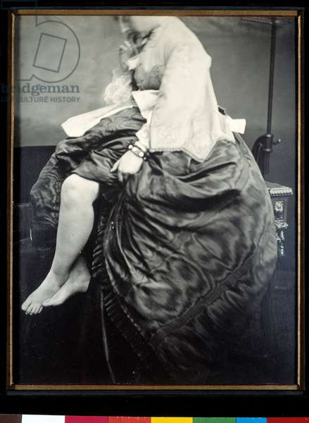 Countess Verasis de Castiglione nee Virginia Oldoini, sitting on a table. The Countess lifts up her dress to denude her legs and feet. Silver gelatin bromide test by Louis Pierson (1822-1913) 1863 Paris, Musee d'Orsay