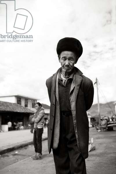 Man wonders on street China (b/w photo)