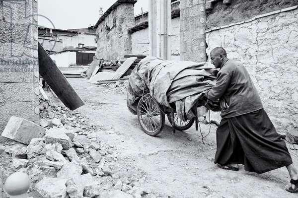 A monk wheels building materials through the Shangri-la Monastery, Yunnan, China (b/w photo)