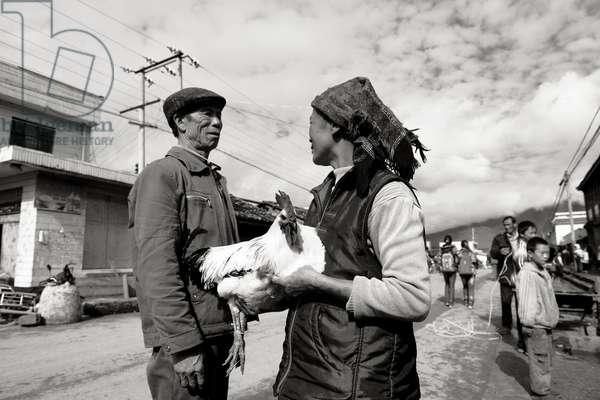 Man and women talk in the streets, near Lugu Lake, China (b/w photo)