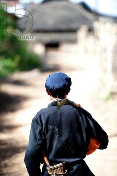 Farmer returns home, Southern China (photo)
