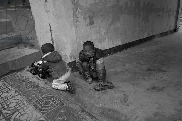 Kids playing in street Deqen, China (b/w photo)