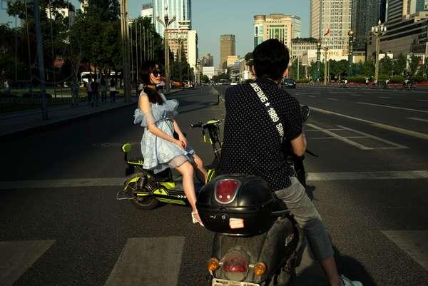 Couple wait at traffic lights, Chengdu, China (photo)