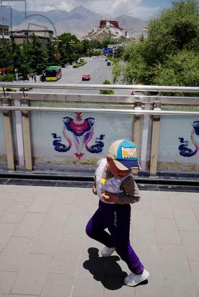 Boy dances in front of Portala palace, Lhasa, Tibet (photo)