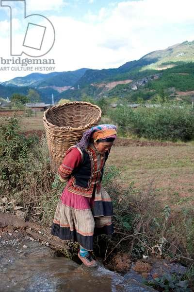 Traditional lady walks home, China (photo)