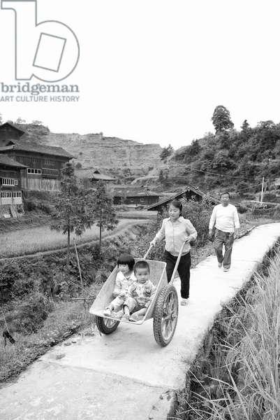 Mother pushes kids in wheelbarrow. Nr Yibin, China (b/w photo)