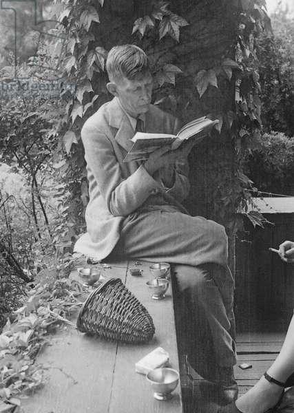 W.H. Auden reading on the verandah, 1940s (b/w photo)