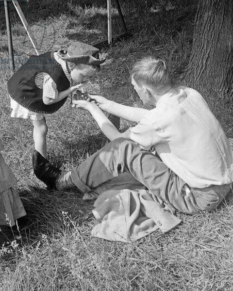 W. H. Auden offering a young boy a light, 1940s (b/w photo)