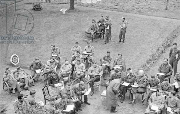 W. H. Auden (reading at bottom centre, no hat) with other Allied servicemen in Darmstadt, Germany, May 1945 (b/w photo)