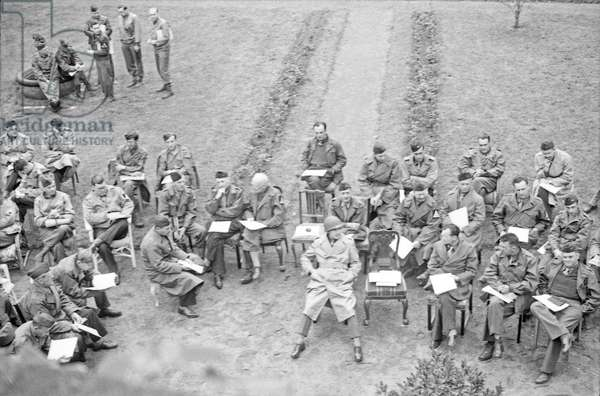 W. H. Auden (reading at bottom left, no hat) with other Allied servicemen in Darmstadt, Germany, May 1945 (b/w photo)