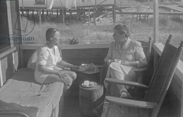 Tania Kurella Stern with a guest in the beach house 'Bective Poplars' on Main Walk, in the town of Cherry Grove, Fire Island, New York, summer 1949 (b/w photo)
