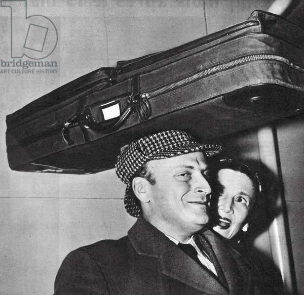 Yehudi Menuhin in playful mood with his violin case perching on his 'Sherlock Holmes' deerstalker hat, 1958 (b/w photo)