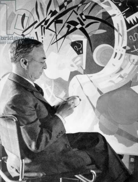 Vassily Kandinsky in his workshop in Neuilly-sur-Seine (France) in front of his canvas Dominant curve, 1936 (b/w photo)