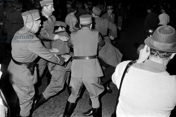Policies arresting a demonstrator in the clashes between left-wing youth organizations and anti-communists on Place Neuve in Geneva, recorded on 14 May 1968 (b/w photo)