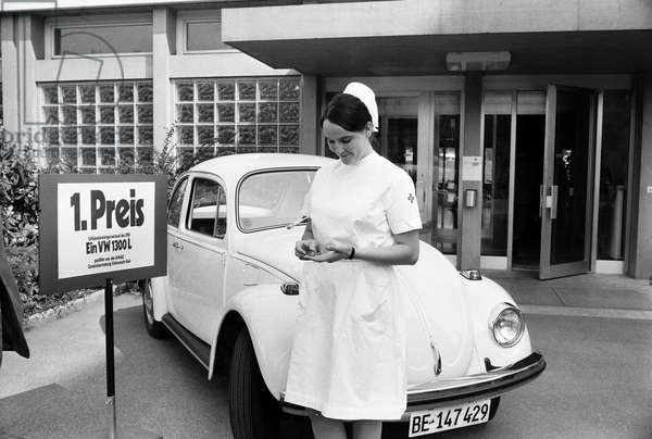 """Sister Annelies holds the car key for the """"Rotkreuz-Kaefer"""", a prize awarded by the Swiss Red Cross SRK, in her hands in front of the Lindenhofspital in Bern on June 13, 1970 (b/w photo)"""
