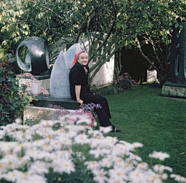 Portrait of Dame Barbara Hepworth (1903-75) seated in her garden next to one of her sculptures (photo)