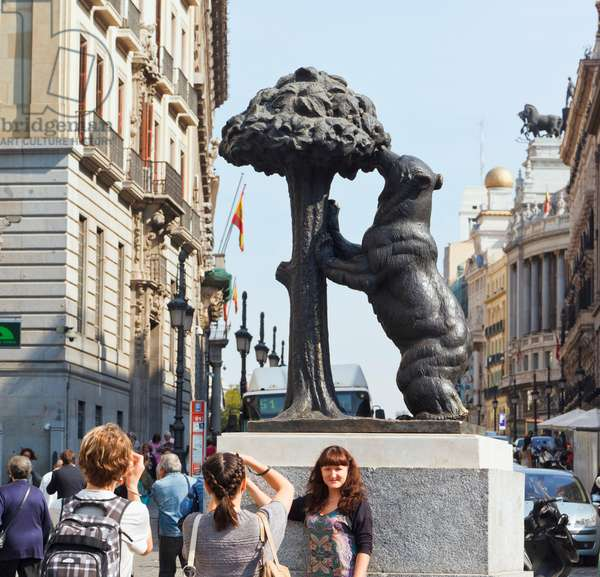 Madrid, Spain.  Puerta del Sol.  Tourists photographing each other in front of statue of Bear and Strawberry Tree - El Oso y El Madroño - from Madrid's coat of arms. (photo)