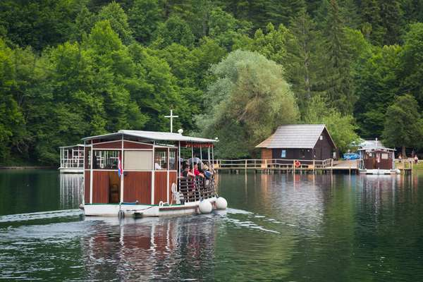 Visitors setting out on an excursion in an electric ferry, Plitvice Lakes National Park, Lika-Senj County & Karlovac County, Croatia, Lakeside (photo)