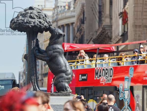 Madrid, Spain.  Puerta del Sol.  Tourists on bus photographing statue of Bear and Strawberry Tree - El Oso y El Madroño - from Madrid's coat of arms. (photo)