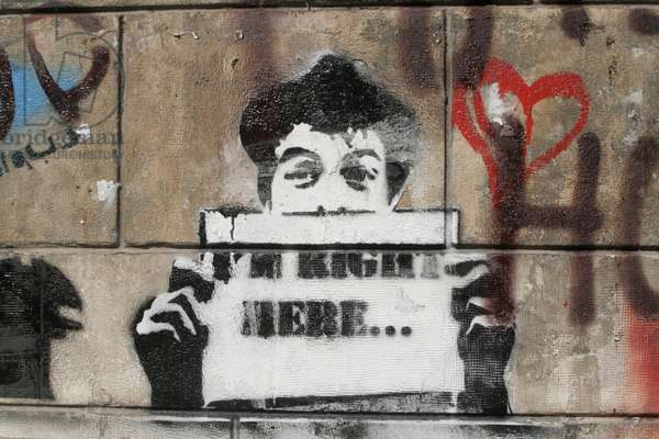 Graffiti depicting a boy holding a sign, 2010 (photo)