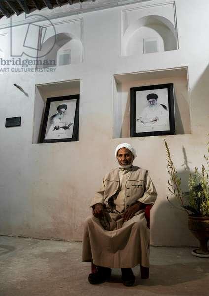Old Bandari Sailor In Front Of Khameini And Khomeini Portraits In A House, Hormozgan, Bandar-E Kong, Iran, 2015 (photo)