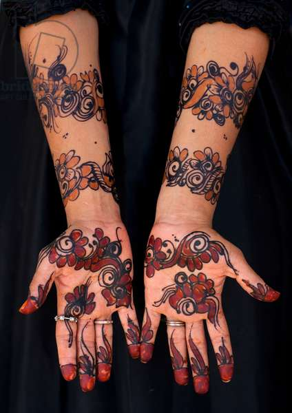 Human palm of hand and forearm of woman drawing patterns with henna and indigo blue, Maulidi festival, Lamu Kenya, Africa (photo)