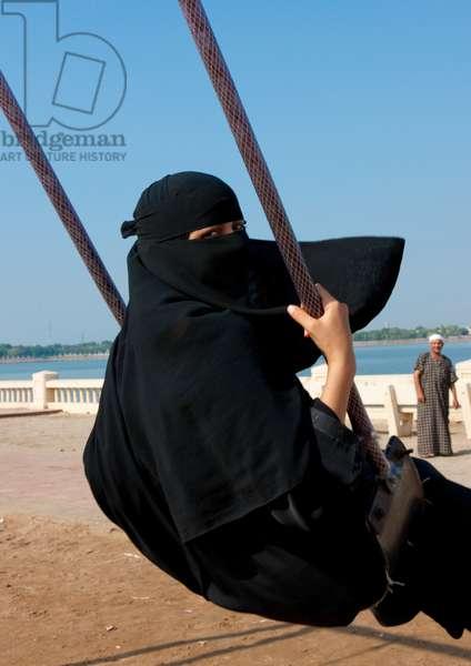 Girl in Abaya on a Swing, Jeddah, Mecca Region, Saudi Arabia (photo)